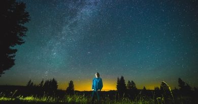 uma pessoa deslumbrada olhando o céu a noite. Comentários quanto as influências da Astronomia.