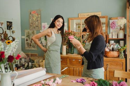 Uma pessoa observando a outra arrumando uma flor. Mostra um Ambiente de Trabalho nas Pequenas Empresas e o Marketing Interno