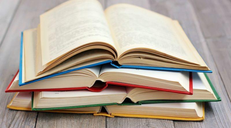 Alguns livros abertos um sobre os outros. Bibliografia e Referências bibliográficas.