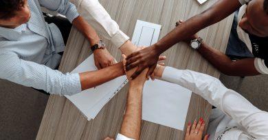 Pessoas com as mãos uma sobre as outras. Distinção entre os Ambientes: Físico e Social na Pequena Empresa