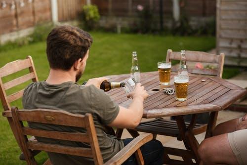 Em uma mesa de madeira redonda e um belo gramado ao redor, dois amigos tomam cerveja. O Cristão e a Bebida Alcoólica: O cristão pode tomar bebidas alcoólicas?