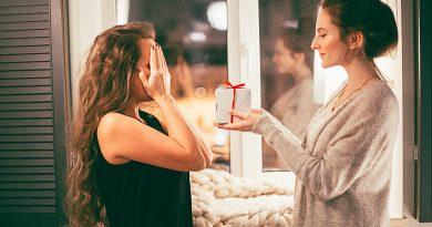 Mulher com o olho fechado e outra vai lhe dar um presente. Uma Mensagem para um Aniversariante mensagem para você.