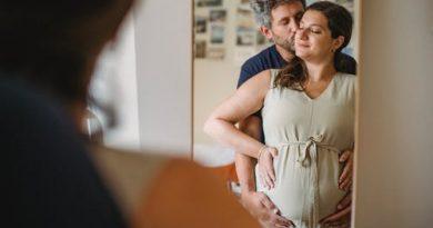 Um casal se abraçando e a esposa grávida foto tirada refletida do espelho. O Que é a Felicidade?