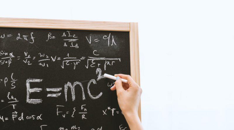 """Uma pessoa escrevendo em um quadro negro a equação E=mc2. A importância da Relação """"Tempo-espaço"""" na Relatividade de Einstein."""