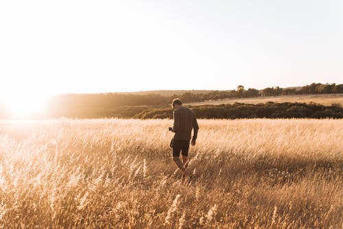 Um homem sozinho no meio de uma plantação baixa. O Homem e a Natureza; uma Dádiva? Um Acaso? E o Ocaso?