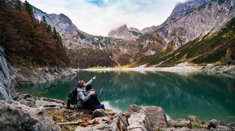 Um casal em um lindo visual cercado por montanhas e um lago abaixo, estão olhando e apontando para o Céu. O esquecimento de nossa origem Cósmica.