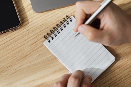 Uma pessoa fazendo anotações em um caderninho. Material Escolar, Livros e Acessórios
