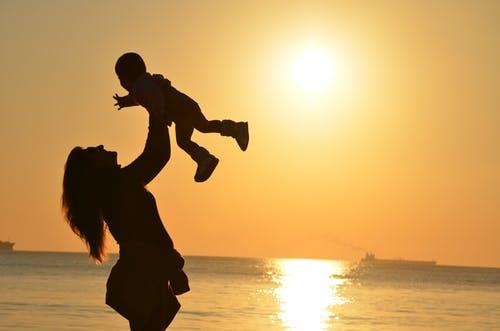 Uma mãe brincando com seu filho o elevando no alto e uma linda imagem do por do sol ao fundo. Homenagem ao dia das Mães