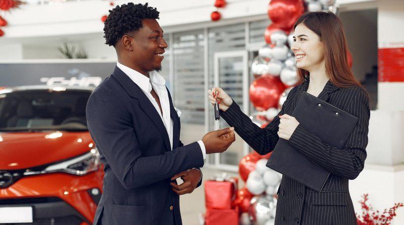 Uma vendedora entrega a chave de um carro ao seu cliente com sorriso no rosto. O que é preciso para ser um bom Vendedor(a), um Vendedor de Sucesso?