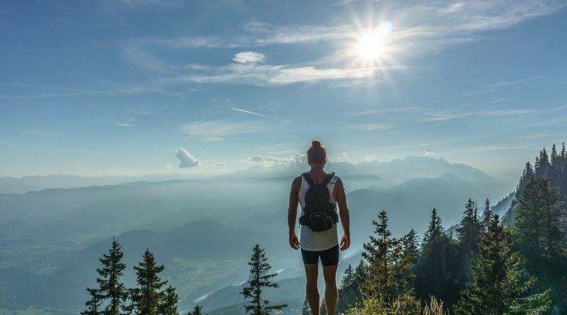 uma pessoa caminha no alto de uma montanha e ao fundo vê uma luz ,o Sol. O Caminho para Deus e a Verdade Quando se fala em Religião