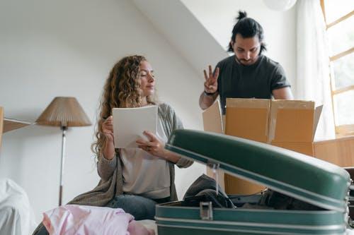 Um casal arrumando as malas para uma vigem. Viagem é investimento