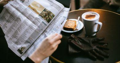 """Uma pessoa lendo em uma mesa com um lindo cafezinho e torradas. Resumo do primeiro dia no Treinamento """"Ambiente de Trabalho e as Relações Interpessoais"""""""