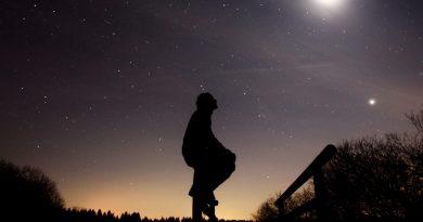 Uma pessoal em perfil no crepúsculo, observando as estrelas. O Sentido da Existência