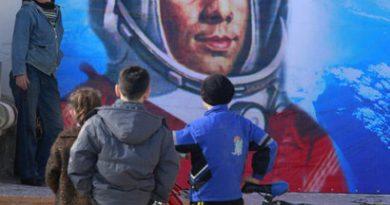 Um grande quadro com a imagem de Yuri Gagarin e três homens à frente um com bicicleta admirando o quadro. Planetário da Gávea comemora 50 anos da chegada do homem ao espaço.