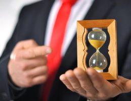 um Executivo apontando para uma ampulheta. Como conseguir mais tempo ou administrar melhor o meu tempo.