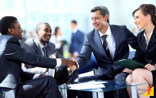 Pessoas em uma mesa se cumprimentando aparentam estar fechando um negócio. A Habilidade da Boa Negociação com Sucesso.