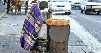 """Uma pessoa maltrapilha pegando lixo em uma lata na rua. O Ser Humano e os sub-humanos ou """"humanóides"""""""
