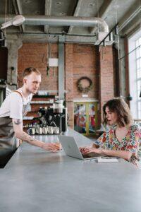 Um homem leva um cafezinho para uma colega de trabalho em um ambiente de trabalho diferenciado e agradável.