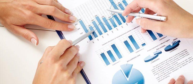 """Uma pessoa está com uma planilha em papel fazendo uma análise de custos. Gestão de Preços. Uma das gestões contidas nos 4 """"Ps"""" do Mix de Marketing."""