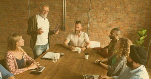 Pessoas em uma mesa tendo orientação de um homem em pé. A Aprendizagem e a Gestão de Equipes