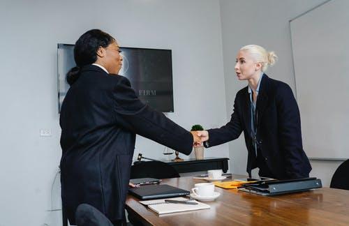 Duas pessoas apertam a mão aparentando troca de confiança. A questão da confiança. Evite frustrações no Ambiente de Trabalho