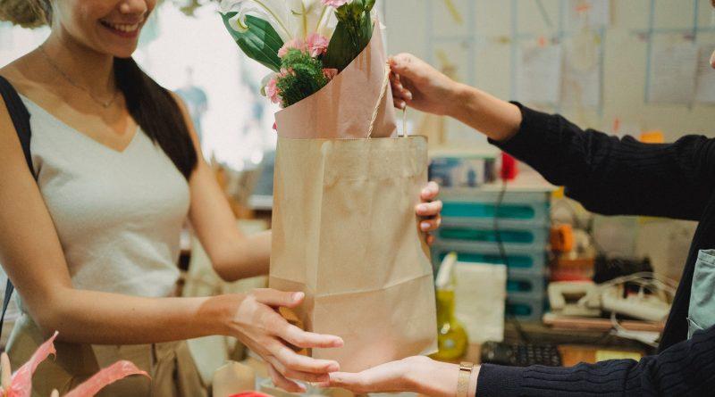 """Atendente entregando uma bolsa com flores. Treinamento, Palestra ou Workshop – """"Venda Mais com Qualidade: Foco no Atendimento ao Cliente"""""""