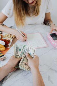 Uma mulher está com uma Calculadora e um caderno fazendo contas enquanto outra pessoa conta dólares.  Estas são dicas e orientações financeiras para se ter uma vida mais tranquila.