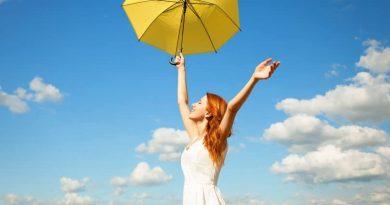 Uma Mulher com uma sombrinha amarela em um lindo céu azul. Viva o Agora. Agora!