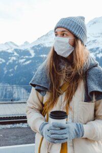 Uma mulher de máscara para se proteger da Covid19 observa uma linda paisagem - montas envoltas em Neve.