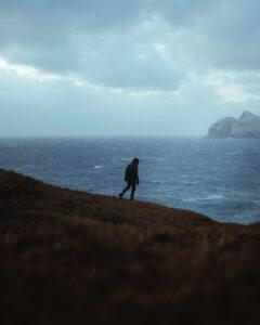 Homem no alto de uma montanha apreciando a vista.