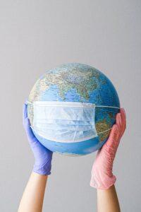 Duas mãos seguram um globo terrestre que está com uma Máscara protetora, a proteção contra a Covid19.
