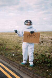 Um homem vestido de Astronauta sinalizando com a Mão pedindo carona com uma Placa escrito Marte.