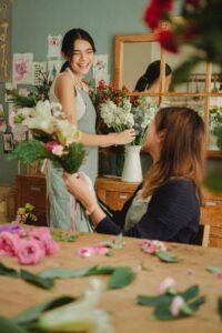 Duas mulheres trabalhando em arranjos de flores de maneira que demonstram estar felizes em uma pequena empresa