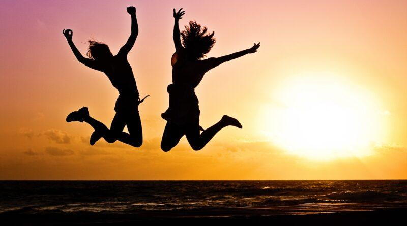Pessoas Pulando e ao fundo um nascer do Sol, lembro que Páscoa é Passagem é pular