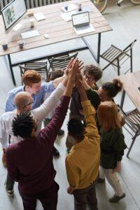 Pessoas estão batendo suas mãos no alto comemorando um feito no trabalho