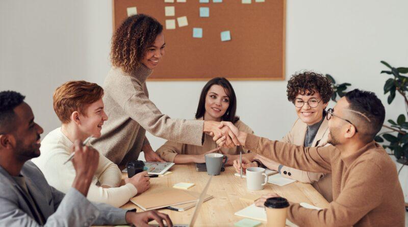 Pessoas em uma ambiente de trabalho se cumprimentando, mostram as relações interpessoais no Ambiente de Trabalho.