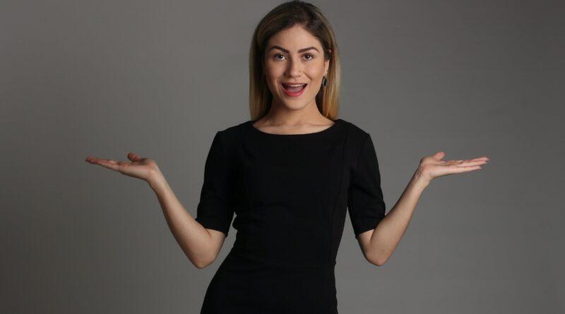 Uma mulher com os dois braços abertos e as mãos com a palma para cima, sinal de quem diz, não sei. Será que a Ignorância é uma benção?