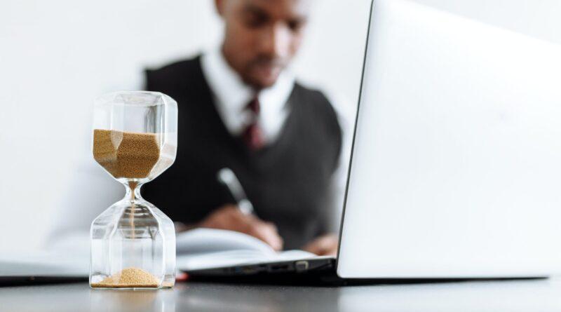 Um homem em usa mesa de trabalho fazendo anotações em um papel e uma ampola do tempo marcando este tempo, como conseguir mais tempo?