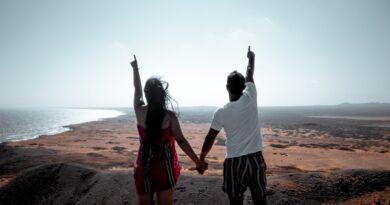 Um casal está em uma bela paisagem apontando para o Céu provavelmente se interrogam, Quem é Deus e quem somos nós.