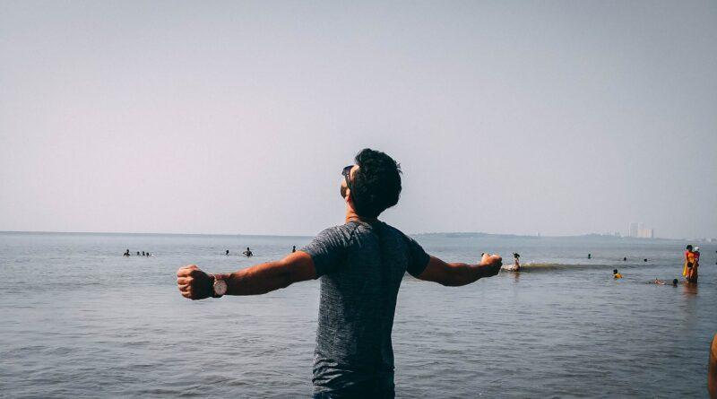 Homem de braços abertos aparenta felicidade olhando um lindo mar cheio de pessoas, quer ser feliz