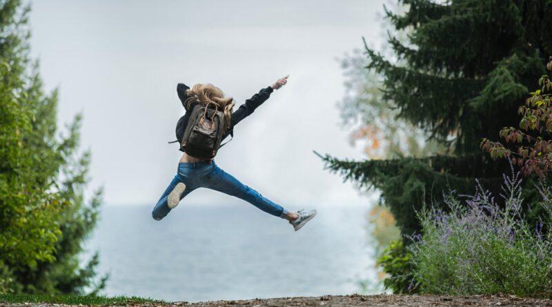 pessoa dando um salto olhando um mar à sua frente, o entusiasmo e a felicidade presentes